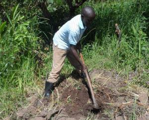 Innocent preparing to plant Moringa seeds in the demonstration garden.